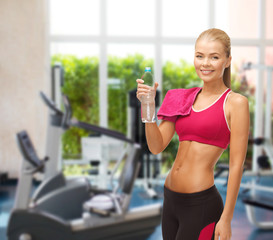 smiling woman with bottle of water at gym