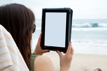 A woman uses a tablet device while on the beach.