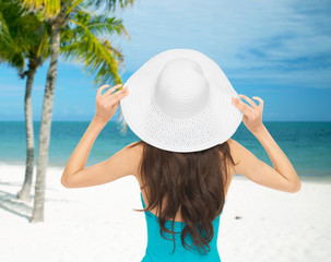 woman sitting in swimsuit with hat