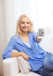 smiling woman with blank smartphone screen at home