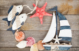 Toy sailboat and fish with seashells and starfish on a wooden ba