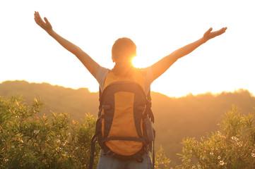 cheering woman hiker open arms at sunrise mountain peak