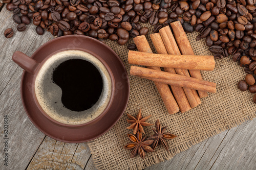 Coffee cup and spices on wooden table