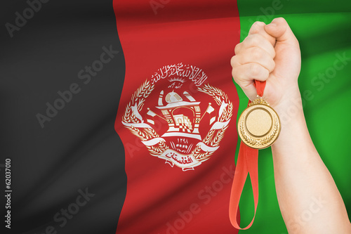 Medal in hand with flag on background - Afghanistan