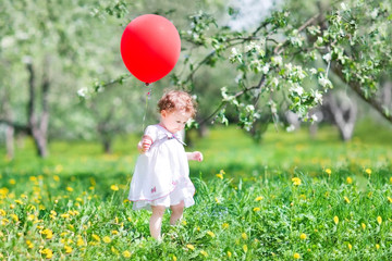 Sweet baby girl playing with a big red balloon