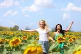 Two young women running through sunflowers