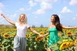 Happy summer girls laughing fun in sunflower field