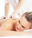 Back of a woman getting spa treatment from a therapist