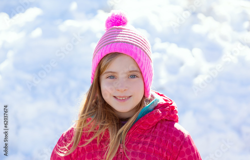 Blond kid girl winter hat in the snow smiling