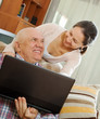 man and mature woman working at his laptop