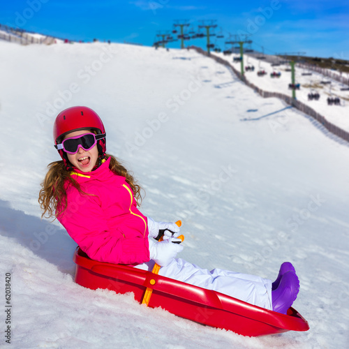 Kid girl playing sled in winter snow