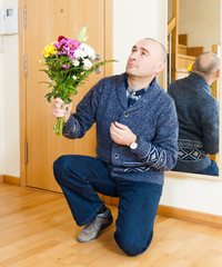 man kneeling with  bouquet of flowers.