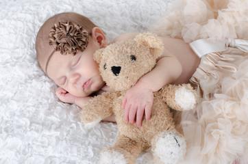 Neugeborenes kuschelt mit Teddy