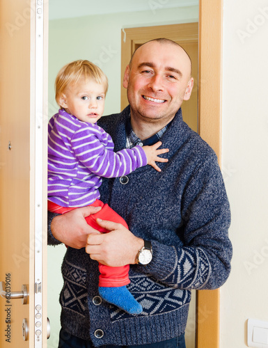 man entering in  apartment with daughter