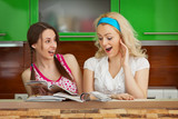 Funny girlfriends browsing magazines on kitchen