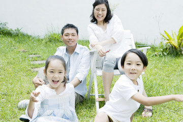 smiling family sitting down on lawn