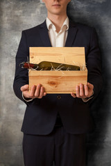 elegant man holding box with wine against concrete wall