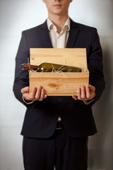 elegant man in black suit carrying wooden box with wine