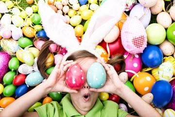 Kind mit Ostereiern vorm gesicht