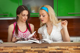 Two girls leaf through  magazines on kitchen