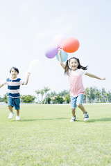 boy and girl holding balloon in their hand