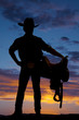Silhouette of cowboy holding saddle at hip