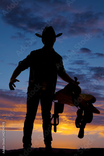 Silhouette of cowboy holding saddle at hip hand out
