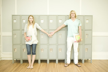 student couple holding hands and standing in front of locker