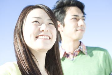 smiling couple under blue sky.