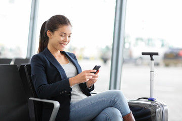 Airport business woman on smart phone at gate