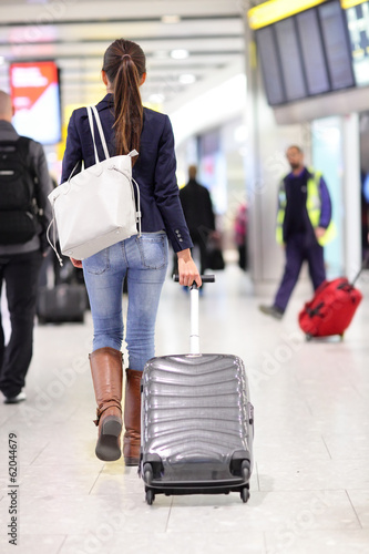 Travel woman walking in an airport with luggage