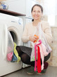 housewife loading the washing machine with laundry bag