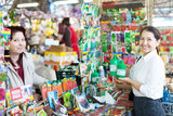 woman selling liquid fertilizer to mature buyer