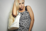 Fashionable beautiful blond woman with white handbag.shopping