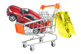 Toy car in shopping cart with hanging gold package isolated on w