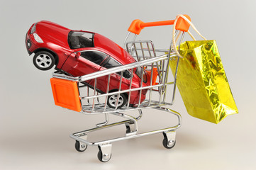 Toy car in shopping cart with hanging gold package on gray