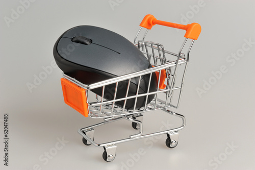Computer mouse in supermarket pushcart on gray