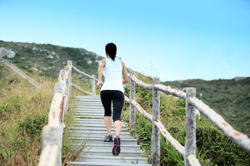 woman running up on mountain stairs to the peak