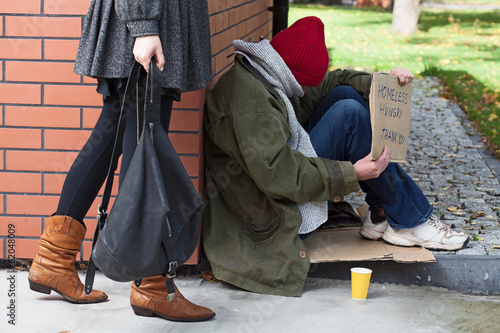 Woman passing by the homeless