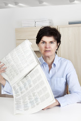 Woman in middle age reading newspaper