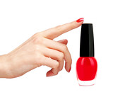 Nail polish of red color and woman hand isolated on white