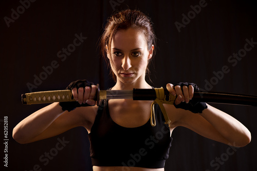 Young Woman Holding Samurai Sword on Black Background.