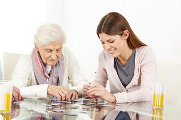 Enkelin spielt Puzzle mit dementer Oma