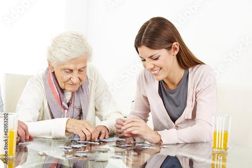 Leinwanddruck Bild Enkelin spielt Puzzle mit dementer Oma
