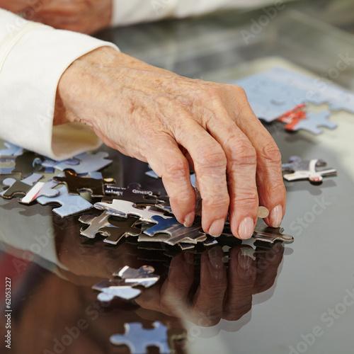 canvas print picture Faltige alte Hand greift nach Puzzlestück