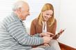 Familie mit Senioren schaut auf Tablet PC