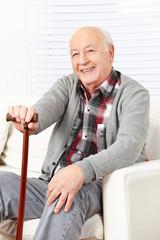 Lächelnder alter Mann mit Gehstock