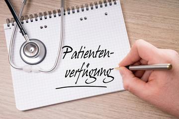 Schreibblock und Hand mit Stift schreibt Patientenverfügung