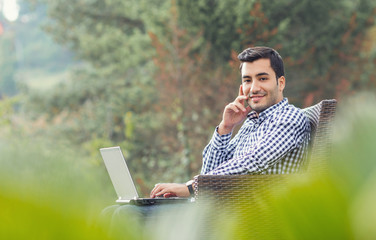 Profile of a young man with laptop, outdoor