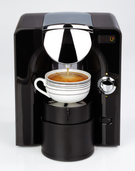 A black modern espresso coffee machine is making a coffee